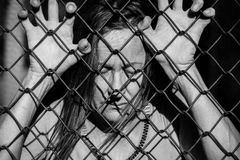 Desperate sad unhappy woman behind fence. Filtered image Portrait of devastated, stressed mature woman with closed eyes and hands gripped on behind mesh wire stock photo