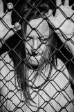 Desperate sad unhappy woman behind fence. Filtered image Portrait of devastated, stressed mature woman with closed eyes and hands gripped on behind mesh wire royalty free stock photos
