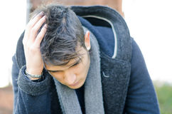 Desperate, sad or upset young man holding his head Stock Image