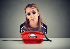 Desperate sad woman waiting for someone to call her. Desperate sad young woman waiting for someone to call her Royalty Free Stock Photos