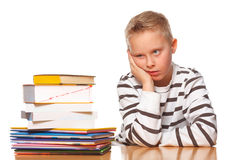 Desperate schoolboy. Schoolboy on desk frustrated of the many books royalty free stock image