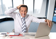 Desperate senior businessman in crisis working on computer laptop at office desk in stress under pressure. Desperate senior businessman in crisis working on Royalty Free Stock Photos