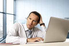 Desperate senior businessman in crisis working on computer laptop at office desk in stress under pressure. Desperate senior businessman in crisis working on Stock Photography