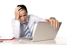 Desperate senior businessman in crisis working on computer at office in stress. Desperate tired senior businessman in crisis working on computer laptop at office Royalty Free Stock Photos