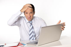Desperate senior businessman in crisis working on computer at office in stress Royalty Free Stock Photography