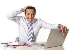 Desperate senior businessman in crisis working on computer at office in stress under pressure. Desperate senior businessman in crisis working on computer laptop Stock Photography