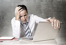 Desperate senior businessman in crisis working on computer at office. Desperate tired senior businessman in crisis working on computer laptop at office desk in Royalty Free Stock Photos