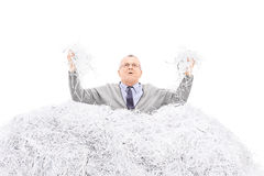 Desperate senior holding a bunch of shredded paper Stock Image