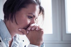 Desperate and sorrowful woman portrait next to window Royalty Free Stock Photo