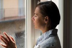 Desperate and sorrowful woman portrait next to window. Woman next to a window looking outside in a lonely mood Stock Image