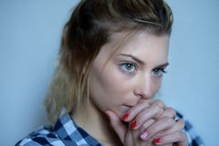 Desperate and sorrowful young girl on background. Portrait of a pensive young woman royalty free stock photos