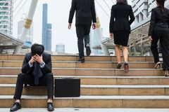 Desperate or Stress Businessman sit on stair. Stress Businessman  sitting on stair of modern city while other Business guys walk upstair. Head down with feeling Stock Images
