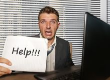 Desperate and stressed business man working overwhelmed at office computer desk feeling helpless and overworked holding notepad. Young desperate and stressed royalty free stock photo