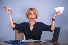 Desperate and stressed business woman working overwhelmed at office desk with laptop computer holding paperwork looking crazy and. Young desperate and stressed stock photography