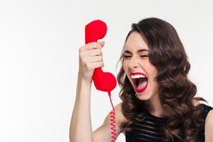 Desperate stressed woman with retro hairstyle screaming in telephone receiver. Desperate stressed curly young woman with retro hairstyle screaming in red Stock Photo