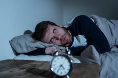 Desperate stressed young man whit insomnia lying in bed staring at alarm clock trying to sleep. Insomnia Stress and Sleeping disorder concept. Sleepless stock image