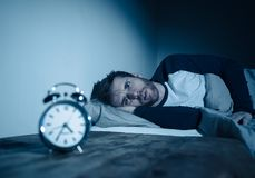 Desperate stressed young man whit insomnia lying in bed staring at alarm clock trying to sleep stock images