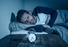 Desperate stressed young man whit insomnia lying in bed staring at alarm clock trying to sleep royalty free stock photos
