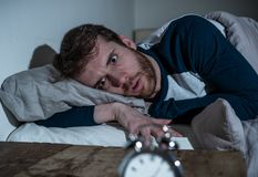 Desperate stressed young man whit insomnia lying in bed staring at alarm clock trying to sleep royalty free stock photography
