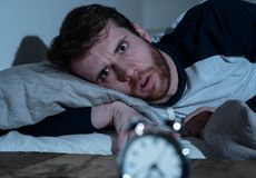 Desperate stressed young man whit insomnia lying in bed staring at alarm clock trying to sleep. Insomnia Stress and Sleeping disorder concept. Sleepless stock images