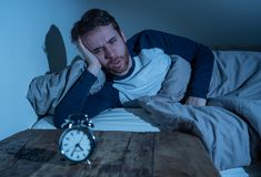 Desperate stressed young man whit insomnia lying in bed staring at alarm clock trying to sleep. Insomnia Stress and Sleeping disorder concept. Sleepless royalty free stock photography