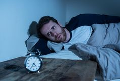 Desperate stressed young man whit insomnia lying in bed staring at alarm clock trying to sleep stock photo