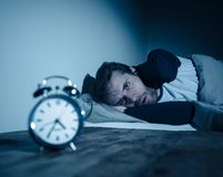 Desperate stressed young man whit insomnia lying in bed staring at alarm clock trying to sleep. Insomnia Stress and Sleeping disorder concept. Sleepless royalty free stock image