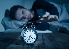 Desperate stressed young man whit insomnia lying in bed staring at alarm clock trying to sleep stock photos
