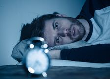 Desperate stressed young man whit insomnia lying in bed staring at alarm clock trying to sleep royalty free stock image