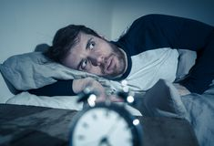 Desperate stressed young man whit insomnia lying in bed staring at alarm clock trying to sleep. Insomnia Stress and Sleeping disorder concept. Sleepless royalty free stock photo