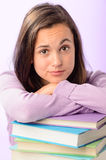 Desperate student girl leaning on stack books Stock Images