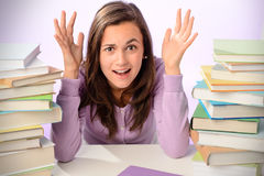 Desperate student girl between stacks of books Royalty Free Stock Photo