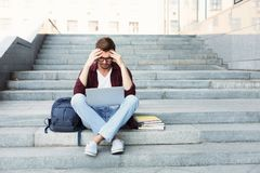 Desperate student sitting on stairs with laptop. Desperate student sitting on stairs and working on laptop outdoors in university campus. Man raised his hands to Royalty Free Stock Image
