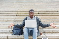Desperate student sitting on stairs with laptop. Desperate student sitting on stairs and working on laptop outdoors in university campus. Shocked african Royalty Free Stock Photo