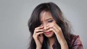 Desperate teenager. Face of desperate young woman crying, on grey background Stock Photo