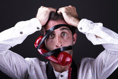 A desperate telephoneman. A desperate man with the phone strapped to the face Royalty Free Stock Image