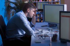 Desperate to finish his work. Shot of a resigned office worker sitting in front of his computer at night Royalty Free Stock Photos