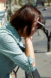 Desperate woman. Is keeping cigarette in  hand, he is covering face Stock Image