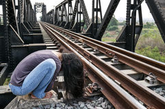 Desperate woman alone beside railway in foetal position, depression, sadness, suicidal crisis. Desperate woman seating alone beside railway in foetal position stock photos