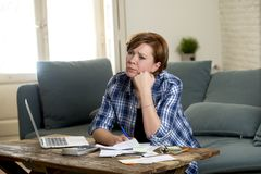Desperate woman banking and accounting home monthly and credit card expenses with computer laptop doing paperwork. Young sad worried and desperate woman banking stock images