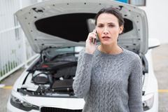 Desperate woman calling for assistance after breaking down Stock Photos
