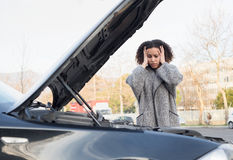 Desperate woman after checking car broken engine Stock Photos