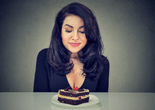 Desperate woman craving cake dessert, eager to eat. Isolated on gray background royalty free stock photos