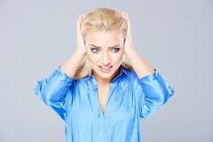 Desperate woman holding her hands to her ears Stock Photo