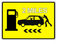 Desperate woman pushing car. Humorous Sign Post 2 Miles to the next Service Station for gas Stock Photography