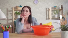 Desperate woman sits at the table and watches as water drips from the ceiling into the bucket. Desperate woman sits at the table at home and watches as water stock footage