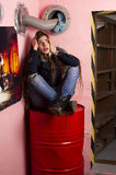 Desperate woman sitting on red barrel. Woman sitting in underground shelter on red barrel with protective mask in her arm. Dramatic expression Royalty Free Stock Images