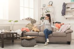 Desperate woman sitting on sofa in messy room. Desperate helpless woman sitting on sofa in messy living room. Young girl surrounded by many stack of clothes royalty free stock photography