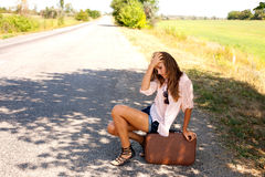 Desperate woman sitting on a suitcase Royalty Free Stock Photography