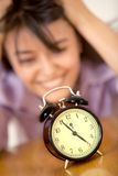 Desperate woman staring at a clock Royalty Free Stock Photos